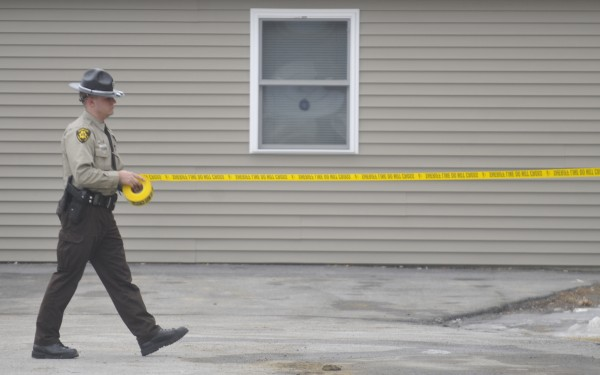 A deputy with the Penobscot County Sheriffs Office cordons the area where shootings took place off outer Hammond Street in Hermon, Thursday, Feb. 16, 2012.