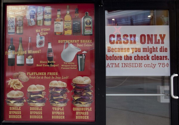 Menu offerings and warnings are posted in the window of the Heart Attack Grill on Fremont Street on Wednesday, Feb. 15, 2012, in Las Vegas.  A man was wheeled out of the restaurant on a stretcher Saturday evening, Feb. 11, 2011 after a medical episode that restaurant employees say looked like a heart attack.
