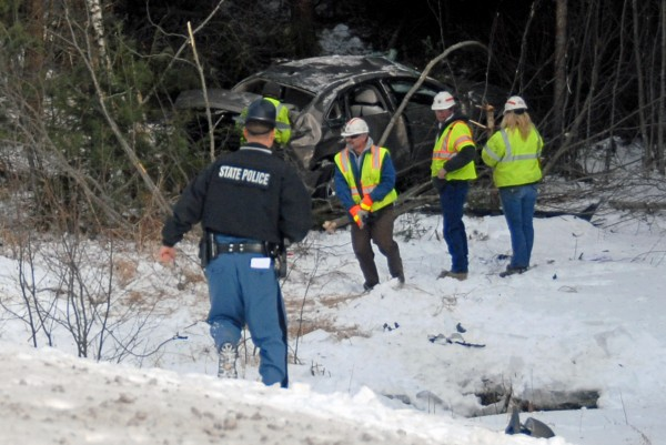Workers mill around a wrecked Chevy Caprice that went off Interstate 95 near Edinburg around 11 a.m. Friday, Feb. 3, 2012. A Massachusetts man was flown by LifeFlight to a Bangor hospital after the accident.