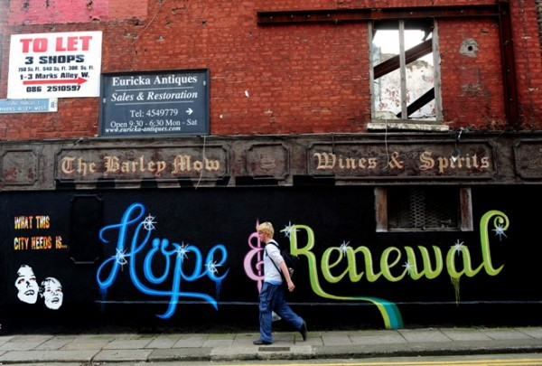 "A Dublin pedestrian walks past a wall covered in graffiti that reads ""Hope & Renewal."" With unemployment stuck at 14 percent, some Irish parents are urging their children to emigrate to find work."