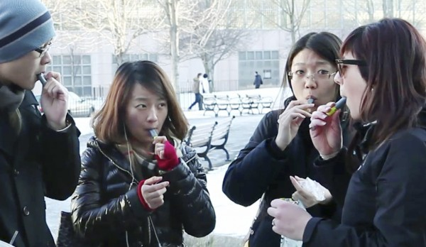In this Monday, Jan. 23, 2012 still photo taken from video, students try free samples of AeroShot, an inhalable caffeine packed in a lipstick-sized canister, on the campus of Northeastern University in Boston. Harvard University engineering professor David Edwards, created AeroShot, which went on the market in late January.
