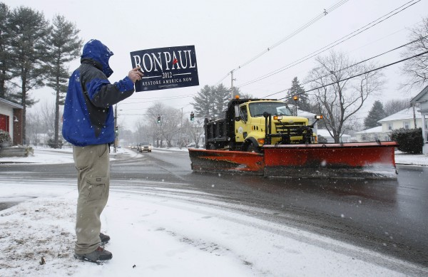 Chris Burton holds a sign in support of Republican presidential candidate Ron Paul outside a caucus, Saturday, Feb. 11, 2012, in Portland.