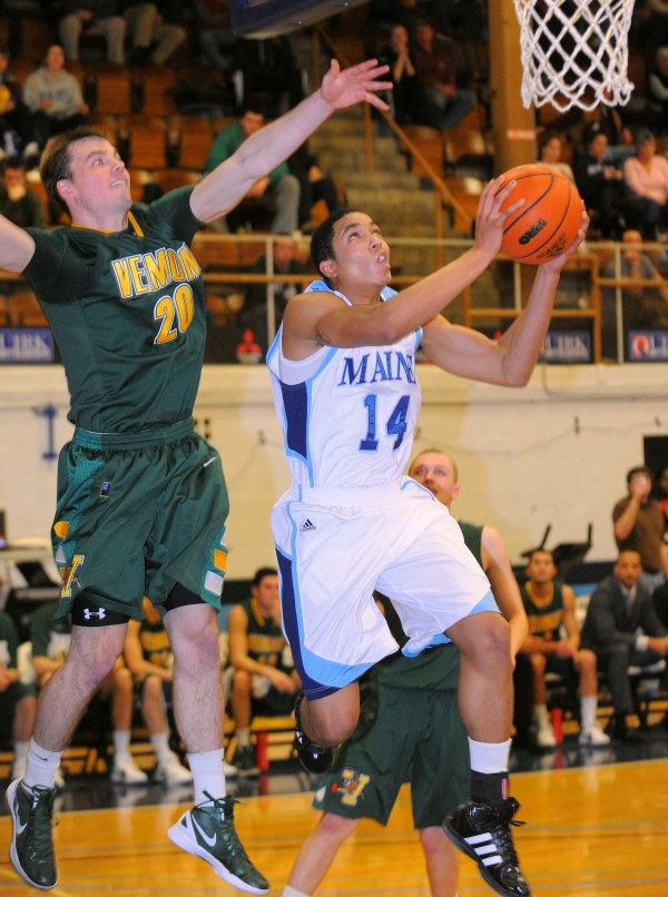 The University of Maine's Justin Edwards drives for the basket past the University of Vermont's Brendan Bald during the first half of the game in Orono Monday.