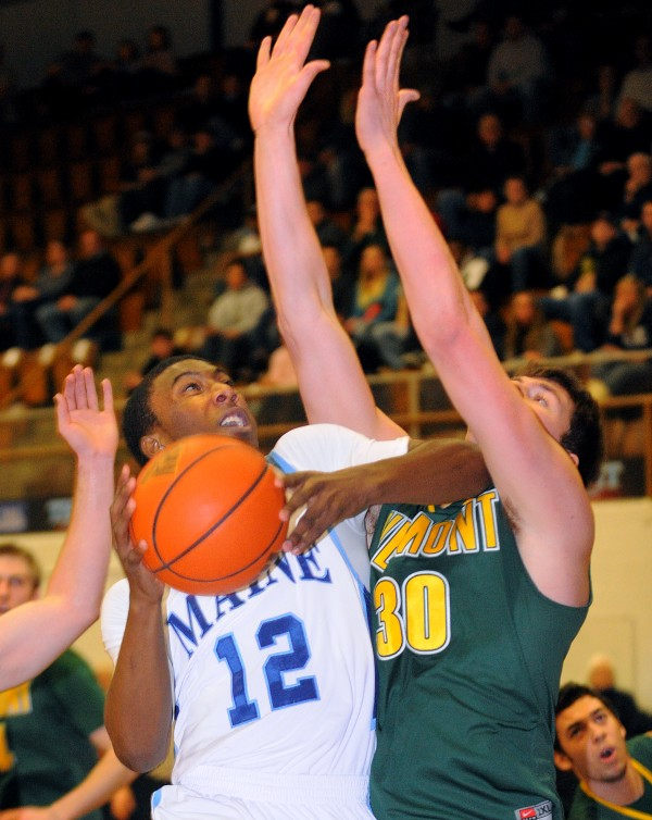 The University of Maine's Xavier Pollard collides with the University of Vermont's Pat Bergmann as he goes up for a shot during the first half of the game in Orono Monday.