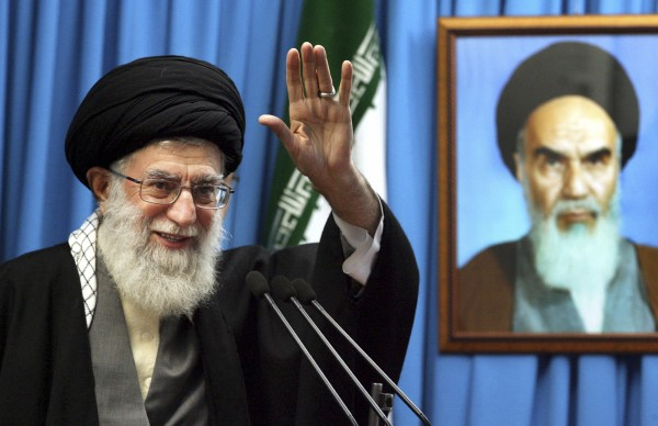 In this Friday, Feb. 3, 2012 file photo released by an official website of the Iranian supreme leader's office, Iranian supreme leader Ayatollah Ali Khamenei waves to the worshippers, in front of a portrait of the late revolutionary founder Ayatollah Khomeini, before he delivers his Friday prayers sermon, at the Tehran University campus, Iran. Ayatollah Ali Khamenei told nuclear experts Wednesday that atomic arms don't bring power but said Iran's progress in nuclear technology has brought national dignity and pride.