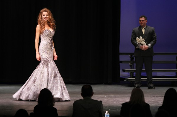 Mrs. Maine-America Pageant winner Cassandra Maureen Provencher of Springvale shows off her evening gown as her husband, Andre, looks on during the Mrs. Maine-America Pageant Sunday, Feb. 5, 2011, in Saco, Maine.