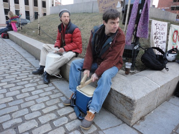 Brian Leonard, executive producer of OccupyMaine's new television show, and fellow occupier Sam Swenson drum beats on plastic containers Wednesday afternoon, Feb. 22, 2012, in Monument Square. The group's rally to celebrate President George Washington's birthday came more than a week after its tent community in Lincoln Park in Portland was taken down.