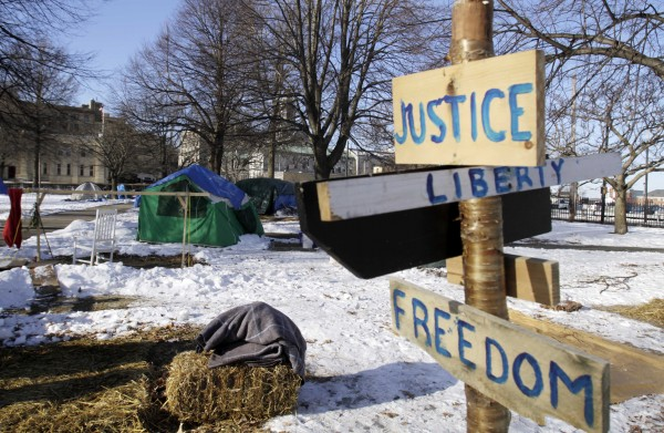 A few remaining tents and signs are seen before being dismantled at the OccupyMaine encampment in Lincoln Park in Portland on Monday, Feb. 6, 2012. A deadline for OccupyMaine to dismantle its encampment came and went Monday morning with no action by police, and several tents remained in Lincoln Park.