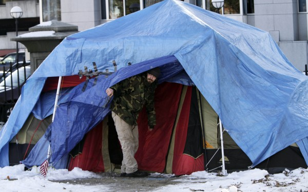 A man looks out from one of the few remaining tents at the OccupyMaine encampment in Lincoln Park in Portland on Monday, Feb. 6, 2012.
