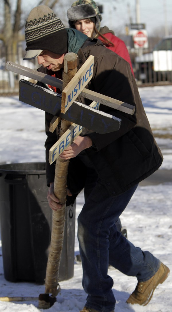 Alan Porter of Portland, Maine, removes a sign as he dismantles part of the Occupy Maine encampment at Lincoln Park in Portland, Maine, Monday, Feb. 6, 2012.