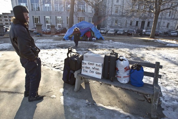 Harry Brown of Portland, Maine, stands next to a bench with packed bags at the Occupy Maine encampment, Friday, Feb. 10, 2012, at Lincoln Park in Portland.