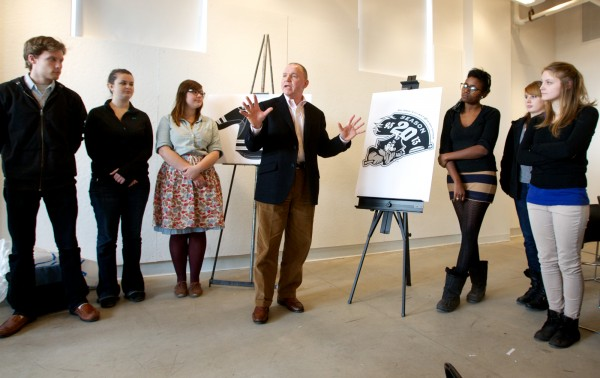 Portland Pirates hockey team CEO Brian Petrovek (center, flanked by students) speaks at a press conference Monday, Feb. 27, 2012, unveiling a new, 20th anniversary logo designed by students at the Maine College of Art.