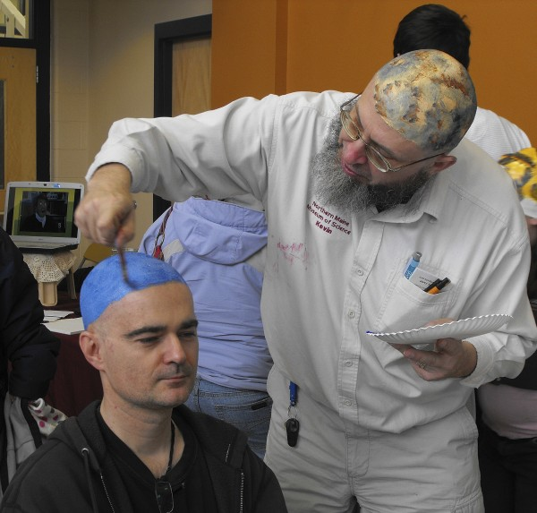 Tomasz Herzog (left) of Presque Isle has his head painted to resemble Neptune by Kevin McCartney, one of the organizers of Planet Head Day at the University of Maine at Presque Isle in 2010.