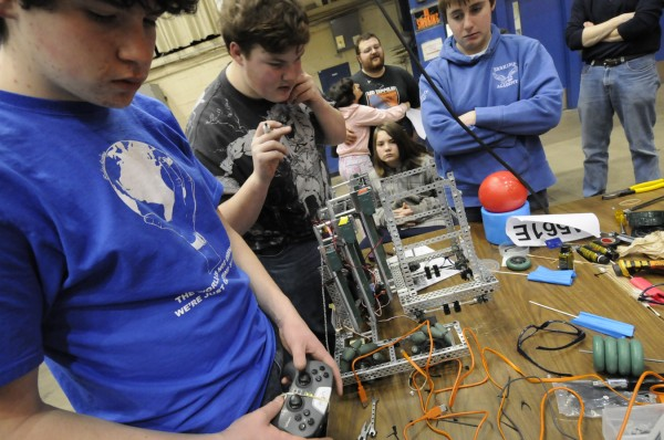 The Erskine Academy physics team, comprised of (from left), Jeremiah Simonsen, Jeffrey Pass, Jordan Bailey and Gary Wentworth (kneeling in center), double check the drive component on their VEX robot before competing in an intermediary round of Saturday's VEX Robotics Competition at the Bangor Auditorium. Behind them are Ben Pass and his fiancee Georgianna Gatcomb, both of Ellsworth, and school staff.