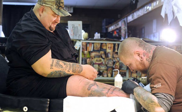 Jon Nisbet of Rumford works on a tattoo for Bryan Lucas at INK, a tattoo shop in Rumford. Lucas' tattoo commemorates his father, a Vietnam veteran and colon cancer survivor.