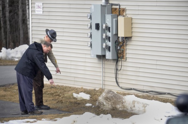 Maine State Police Trooper David Yankowsky (left) and Penobscot County Sheriffs Deputy William Sheehan point to something in the grass as they look for evidence near the scene of shootings at the Duran Apartments in Hermon Thursday morning, Feb. 16, 2012.
