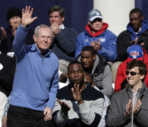 New York Giants quarterback Eli Manning (right) and defensive end Justin Tuck (center) applaud as head coach Tom Coughlin is introduced to the crowd during a ceremony for the NFL football Super Bowl XLVI champions at City Hall in New York, Tuesday, Feb. 7, 2012.