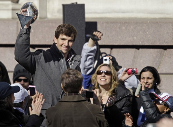 Fans react as New York Giants quarterback Eli Manning hoists the Vince Lombardi Trophy during a ceremony for the NFL football Super Bowl XLVI champions at City Hall in New York, Tuesday, Feb. 7, 2012.