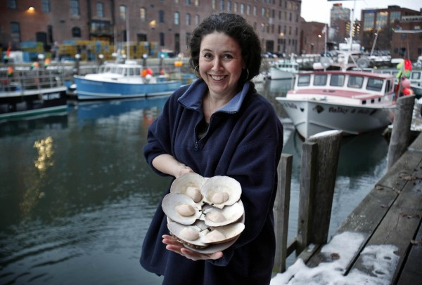 Togue Brawn poses with a plate of scallops on the half shell in Portland, Maine.