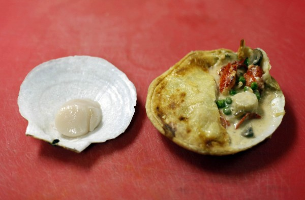 A baked seafood pot pie on the half shell, with ingredients that include scallop, lobster, and vegetables, is alongside a freshly caught scallop on the half shell, at J's Oyster Bar in Portland, Maine.