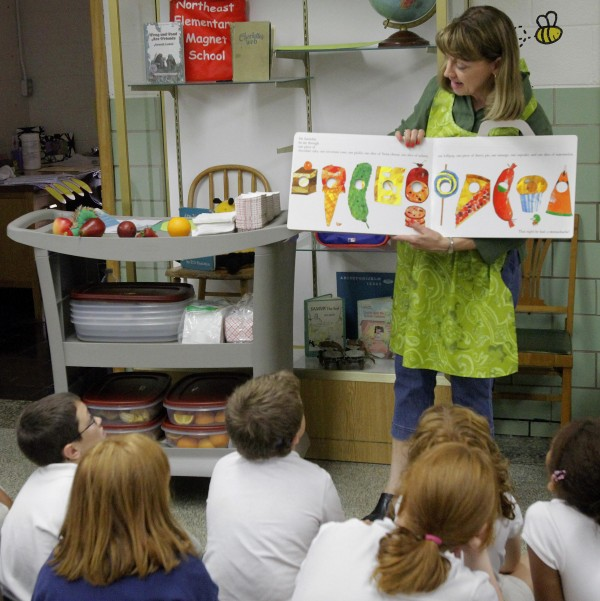 In this Sept. 20, 2011 file photo, Nancy Henderson, home economic coordinator for the fresh fruit and vegetables program, reads a story to students before they receive fruit snacks during a lesson in healthy eating at Northeast Elementary Magnet, in Danville, Ill. Northeast offers no junk food for sale to its students, but a new study found that almost half the nation's elementary schools do.