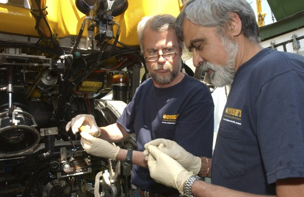 This April 2007 photo provided by Odyssey Marine Exploration, shows Odyssey co-founder Greg Stemm, left, and project manager Tom Dettweiler examining a coin recovered from the &quotBlack Swan&quot shipwreck by Odyssey Marine Exploration. The transfer of 17 tons of shipwreck treasure wrested away from Odyssey to the Spanish government will be made later this week from a U.S. Air Force base in Florida, officials confirmed Tuesday night, Feb. 21, 2012.
