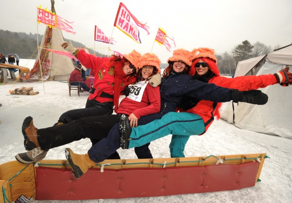 Members of the Hot Mamas toboggan team, left to right, Heather Hearst, Kate Cohen, Diana Castle and Marianne Forti pose for a picture in front of their ice encampment on Hosmer Pond.
