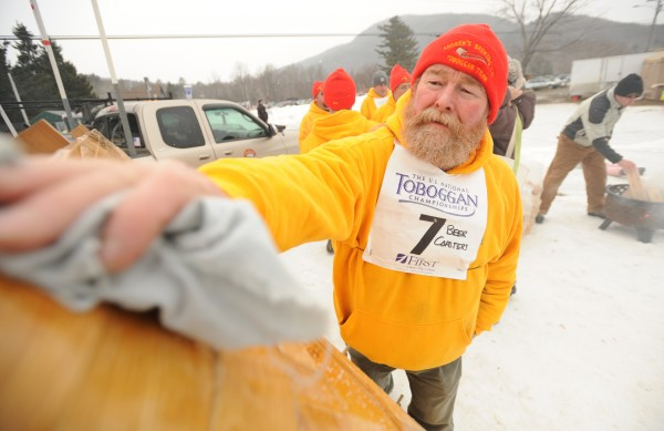 Jim Tyler of Searsport, a 15-year racing veteran who is part of the two-man toboggan team Beer Coasters, applies wax to the bottom of a toboggan. Wax type is a closely guarded secret among the serious toboggan competitors.