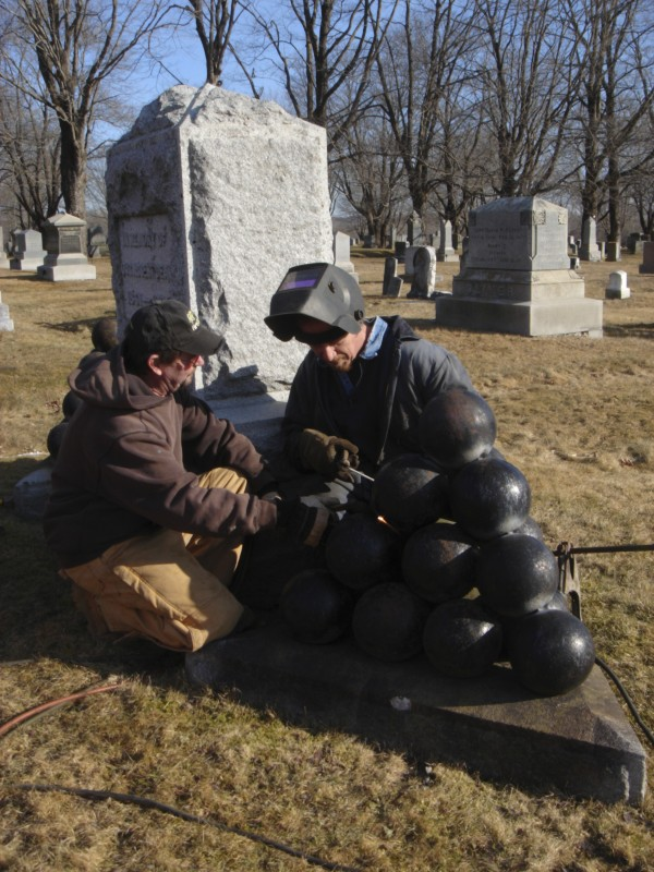 Thomaston Public Works employees Mike Davis (left) and Cliff Eugley (right) work to secure cannon balls at the GAR Civil War monument at the Thomaston Village Cemetery in Thomaston on Thursday, Feb. 9.