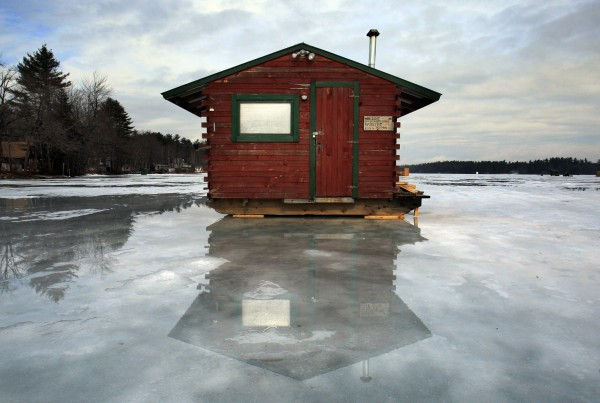 A fishing shack is reflected in a puddle on Crystal Lake in Gray on Thursday, Feb. 23, 2012. The lake was quiet on Thursday but as many as 5,000 anglers are expected on Saturday for an ice-fishing derby. The derby had to be rescheduled from last month due to a lack of ice. Despite the rain, the ice remains about 14 inches thick.