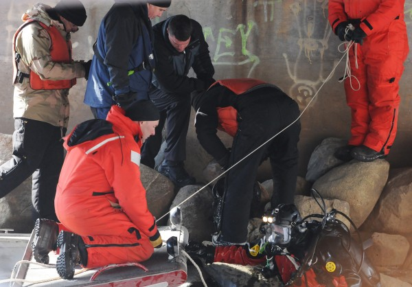 State Police dive team members along with detectives gather around a backpack that was pulled up from the Messalonskee Stream near the North Street Bridge in Waterville on Friday, Feb. 3, 2012. The backpack contained items that led police to believe it belongs to a Waterville High School student from 2006. They also found an opened safe and a knife. They determined neither were related to the Ayla Reynolds case.