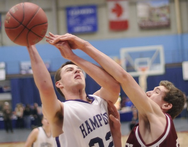 Hampden boys basketball player Logan Poirier (32) puts up a first half shot and is fouled by Bangor player Alex Clark (40) as they near the half way mark in their Class A playoff game in Augusta on Wednesday, Feb. 22, 2012.