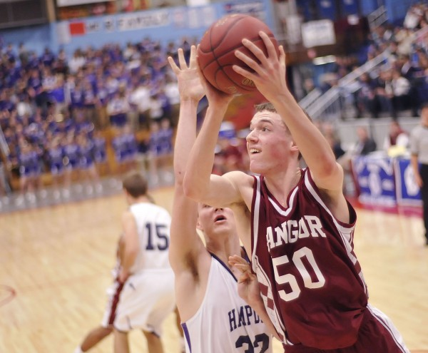 Bangor boys basketball player Patrick Stewart (50) turns and fires a shot over Hampden defender Logan Poirier (32) in the first half of their Class A playoff game in Augusta on Wednesday, Feb. 22, 2012.