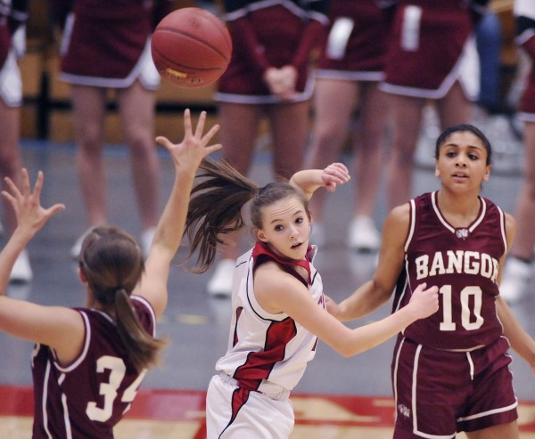 Bangor girls basketball player Denae Johnson (10) passes the ball to teammate Jordan Seekins (34) over the head of Cony player Emily Quirion (11) in the first half of their Class A playoff game in Augusta, Maine, Friday, Feb. 17, 2012.