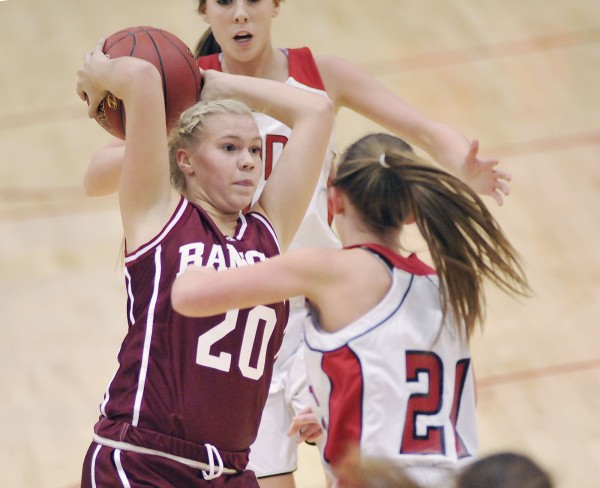 Bangor girls basketball player Elizabeth Hintz (20) passes off under pressure form Cony player Bethany Elwell (21) in the first half of their Class A playoff game in Augusta, Maine Friday, Feb. 17, 2012.