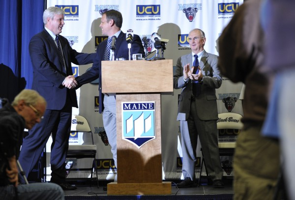 Newly appointed University of Maine women's basketball coach Richard Barron (center) received a hearty congratulations from University of Maine Athletic Director Steve Abbott (left) as University of Maine President Robert Kennedy and others applaud Barron during Tuesday's press conference at the the Orono campus to introduce him to the university community.