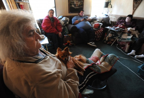 Eleanor Hartshorn sits with her dog Toby in a trailer owned by Patricia LeSan on  on Thursday, Dec. 29, 2011. With her is Becky Nibby, second from left, Luman LeSan, center and his sister Betsy LeSan. Hartshorn was burned out of a mobile home she shared with Becky Nibby, Betsy LeSan and Pam Nibby.