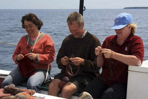 Passengers aboard the schooner J and E Riggin enjoy knitting while sailing on Penobscot Bay last summer. Knitting cruises have become a popular segment of the vessel's seasonal cruising schedule.