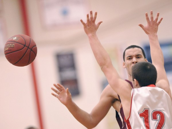 Camden Hills' boys basketball player Adam Carlsen (12) puts the brakes on Washington Academy player Christos Iliopoulos-Ontoemelam in the first half of their game in in Camden, Maine, on Wednesday, Feb. 15, 2012.