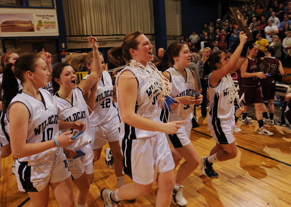 Members of the Presque Isle girls basketball team parade their Eastern Maine Class B trophy around the floor of the Bangor Auditorium on Saturday, Feb. 25, 2012 after defeating Nokomis.