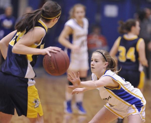 Washburn High School girl's basketball player Mackenzie Worcester (14) keeps her hands in the way of  Van Buren's Parise Rossignol (22) in the first half of their Class D semi-final game in Bangor, Maine, Thursday, Feb. 23, 2012.