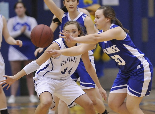 Hodgdon girls basketball player Mariah Wiley (30) dishes off under pressure from Central Aroostook girls player Victoria McIntyre (34) in the first half of their Class D playoff game in Bangor, Maine Thursday, Feb. 23, 2012.