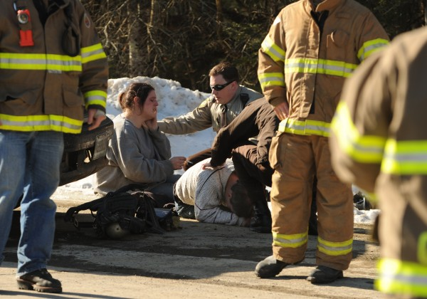 Amanda Rand (second from left) and her husband Nicholas Rand (on ground) are comforted by Penobscot County Sheriff deputies, Andy Whitehouse (third from left) and Sgt. William Sheehan (third from right) after being stopped at the entrance to their driveway in Corinth on Friday, Feb. 10, 2012 and being informed about the death of their 7-year-old son Christian Rand, who died in a fire at the family's camper trailer.