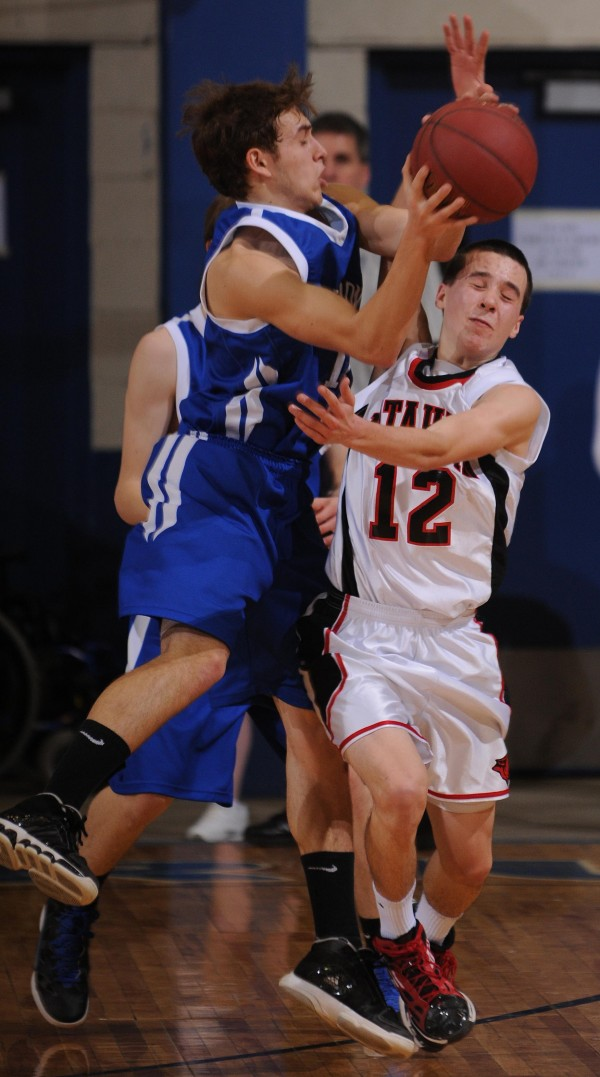 Hodgdon's Nicholas Lunn (left) collides with Katahdin's William Livezy during Class D quarter final action on Monday, Feb. 20, 2012 at the Bangor Auditorium.