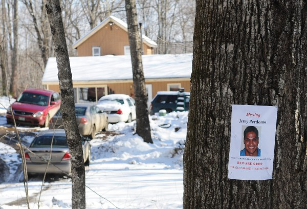 A missing person's poster, featuring Florida firefighter Jerry Perdomo, hangs on a tree outside the home of Gary Porter's Jackson home as unmarked police cars fill the yard on Tuesday, Feb. 28, 2012. Daniel Porter, Gary's son, was arrested at the home late Tuesday afternoon and charged with the murder of Perdomo.
