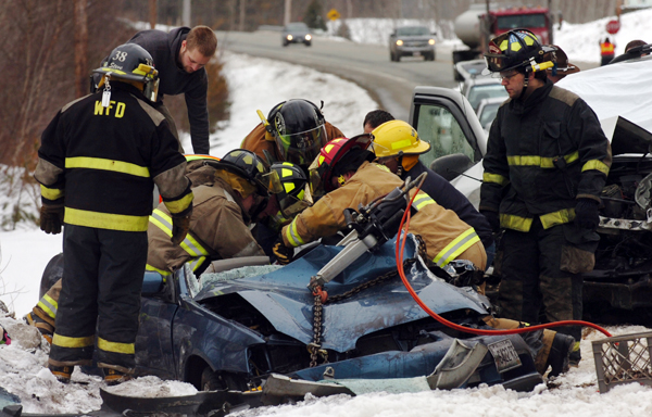 Emergency crews work to remove Louise Boudreau-Bouchard from her vehicle after she was hit head-on by an SUV driven by William Hinkle Jr. while heading northbound on Route 1A in Frankfort around 9 a.m. on Wednesday, March 23, 2011.