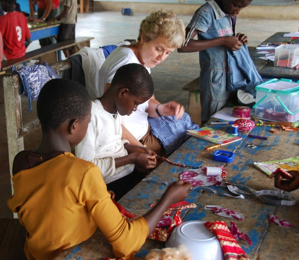 Betty Jamison, a teacher at the William S. Cohen School in Bangor, teaches children to sew seams, make button holes and make simple clothing at the Baptist Orphanage and School Complex in Ghana during the summer of 2008. Pictured are Dorcas (left to right), Doris, Jamison and Bertha.