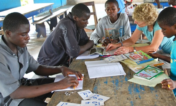 "Augustine (left to right) practices geometry, Emmanuel works to read a book and Willy is writing his book report and working on editing. Doris listens to Emmanuel read with Kristine Reid, also known as ""Mama Kris,"" teacher at William S. Cohen School in Bangor, at the Baptist Orphanage and School Complex in Ghana in 2008."