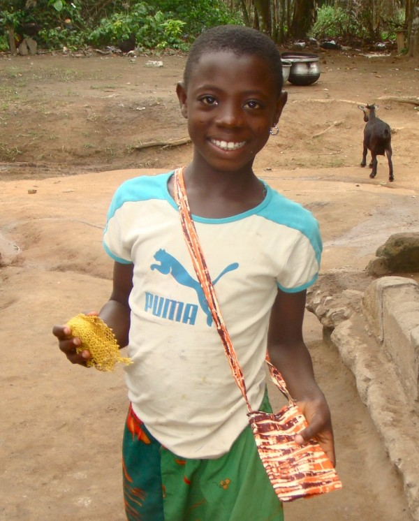Sondra, who lives at the Baptist Orphanage and School Complex in Ghana, shows off her new purse, which she sewed with the help of Betty Jamison, a teacher at the William S. Cohen School in Bangor, during the summer of 2011.