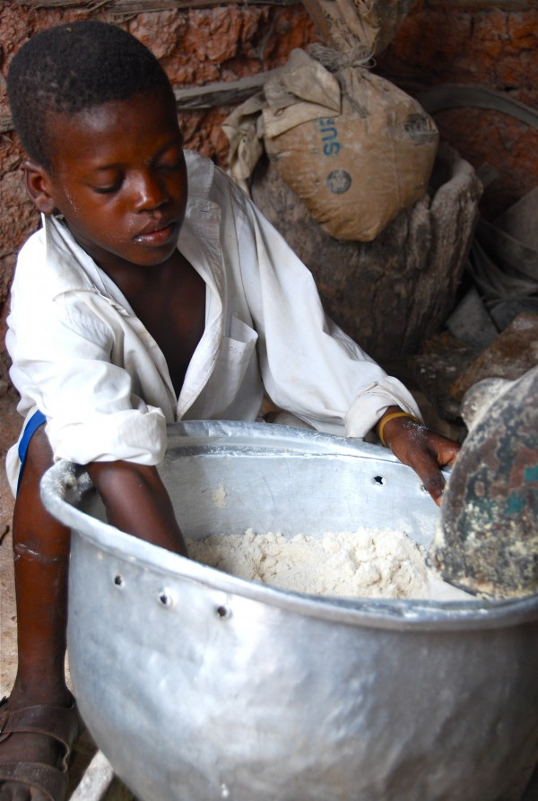 Jacob, who lives at the Baptist Orphanage and School Complex in Ghana, helps pack ground corn flour into bowls as it comes out of the grinder at the corn mill in 2008.